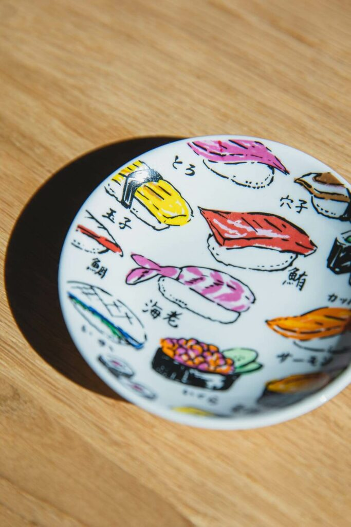 A modern rendition of Japanese ceramics, a colorful plate decorated with paintings of sushi.