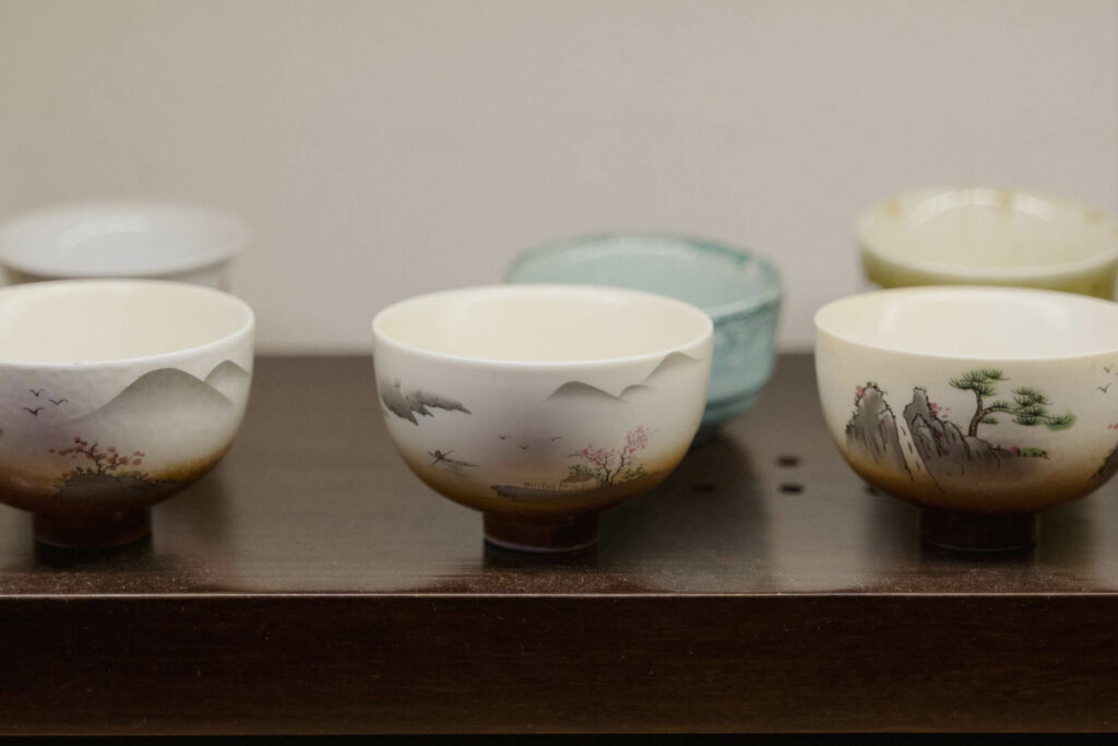 A variety of Japanese ceramics on a wooden table.