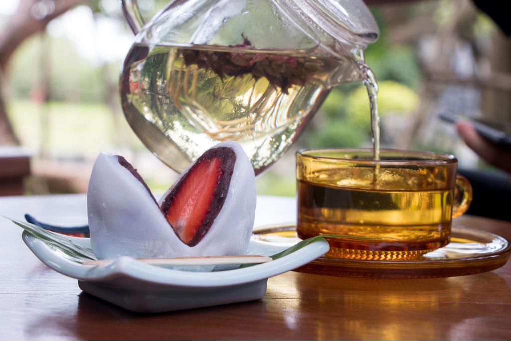 A strawberry daifuku infront of a tea pot.