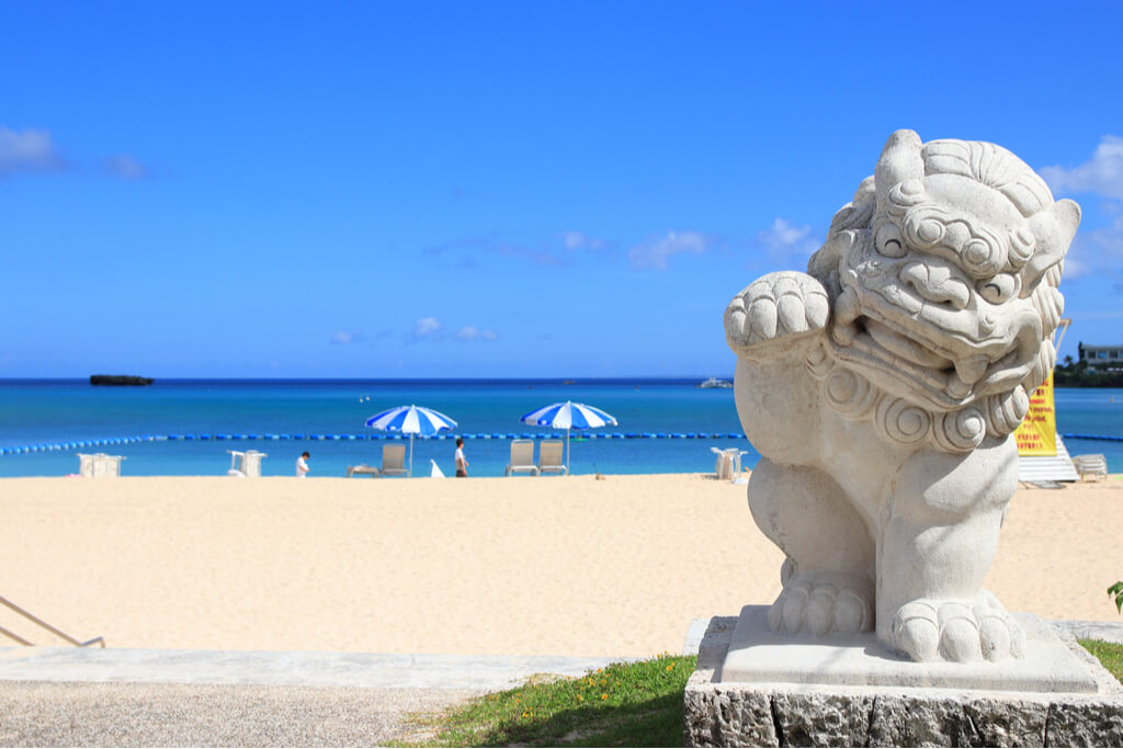 A Japanese guadian statue in front of a beautiful beach.