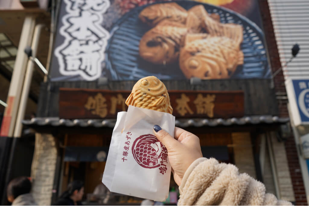 Woman's hand holds up a taiyaki in front of a taiyaki shop in Osaka.