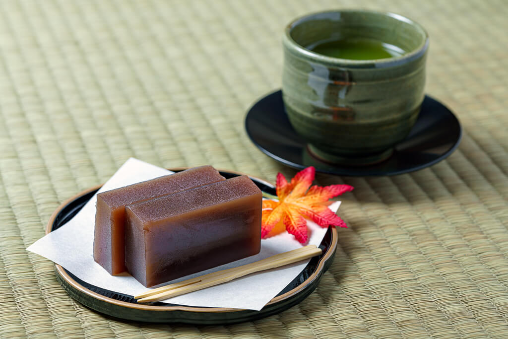Red bean yokan on a plate next to a cup of green tea