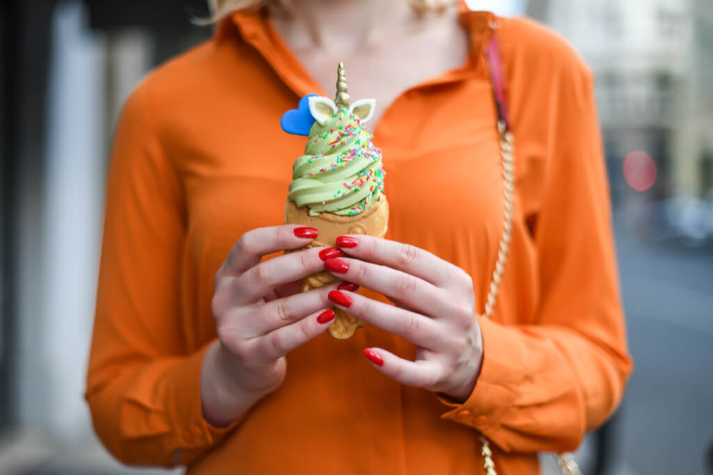 A woman in an orange shirt holds taiyaki filled with ice cream topped with a unicorn horn and a blue heart