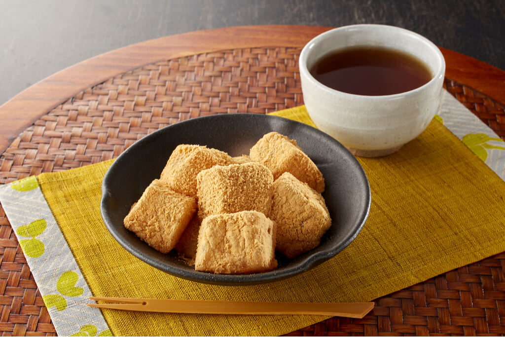 A small bowl of kinako-covered mochi next to a cup of tea.
