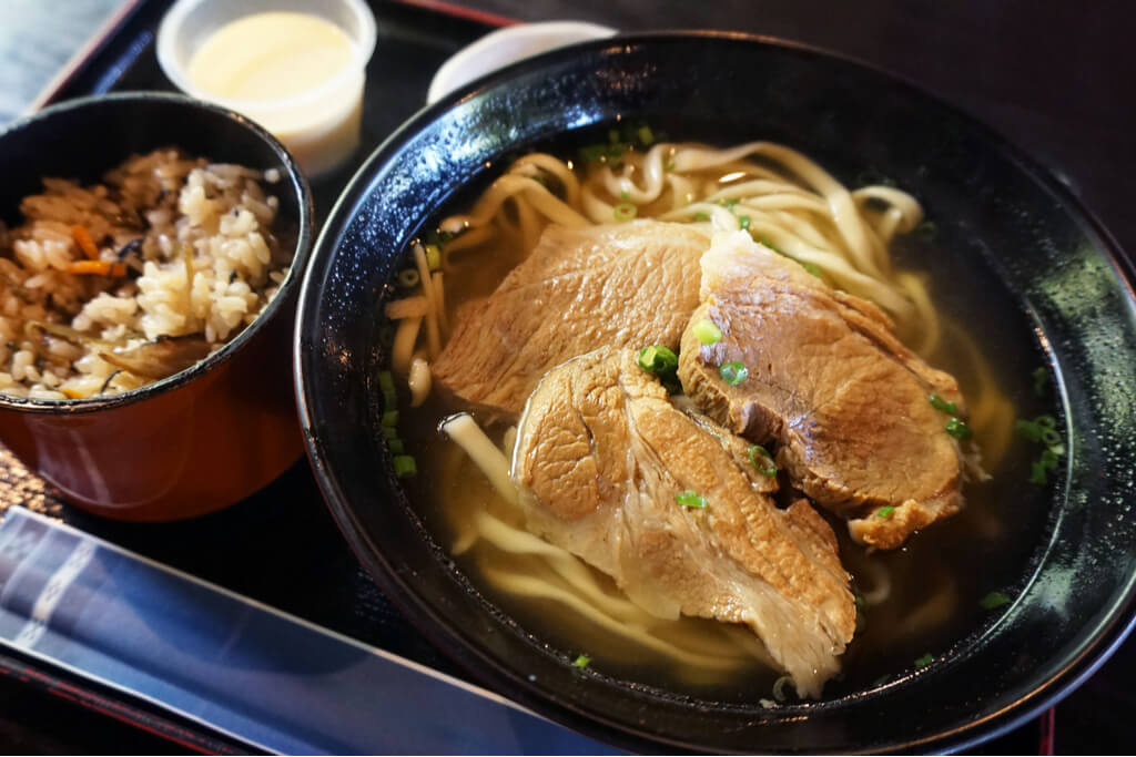 Okinawan soba topped with braised pork next to a bowl of rice.