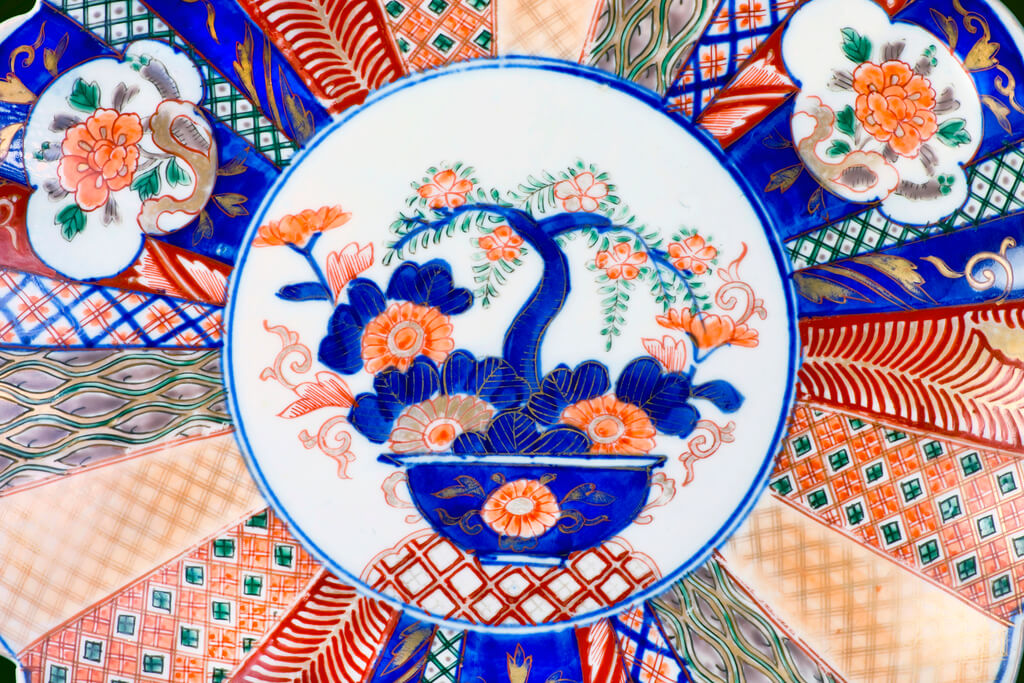 A close-up of an antique imari ware from Japan 1860 with an illustration of a tree among flowers in the middle of several patterns