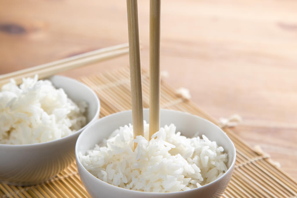 Two bowls of rice on a bamboo placemat on a wooden table with one bowl having a pair of chopsticks sticking upright in them.