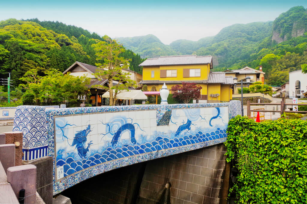 A porcelain bridge in Imari where Imari ware is made, with houses and mountains with trees in the background
