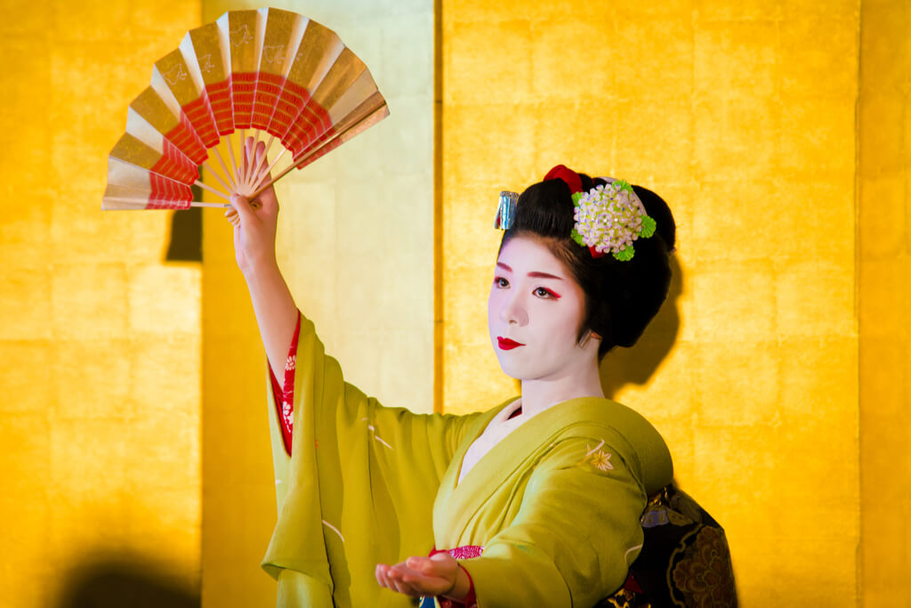 A geisha in a green kimono does a traditional dance with a gold and red fan in front of a gold background.