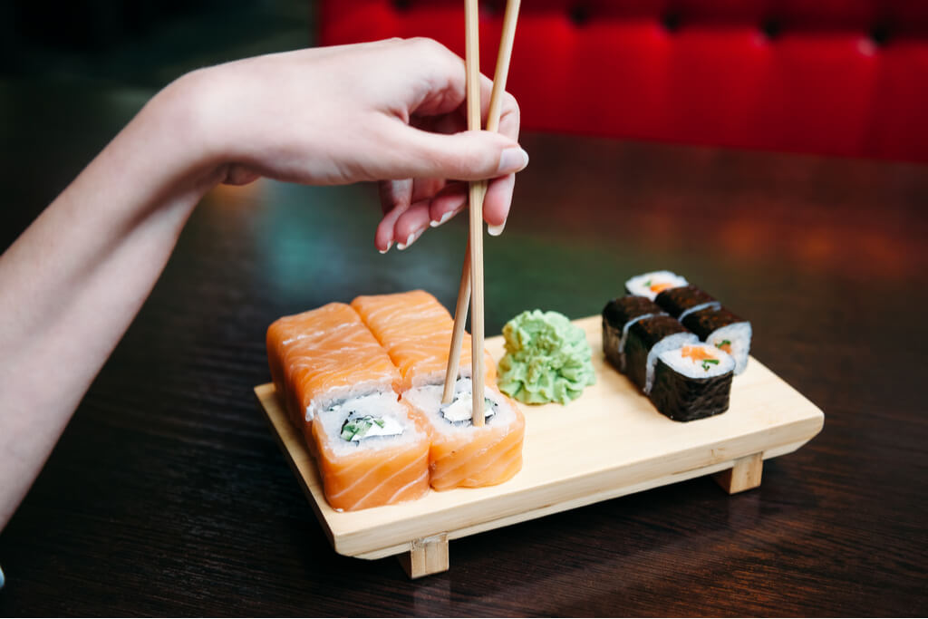 A woman's hand stabs a sushi roll with her chopsticks in a restaurant.