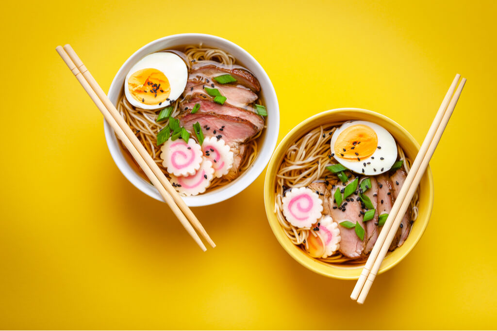 Two bowls of ramen with chopsticks laid across the bowls on yellow background