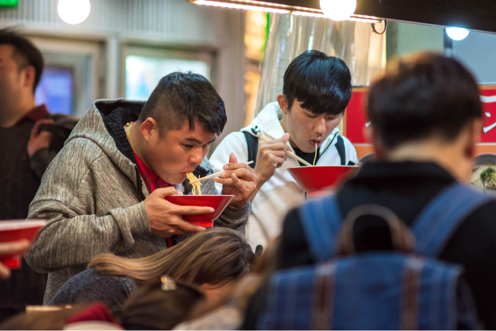 Two men stand in a busy ramen shop and eat noodles out of a red bowl.