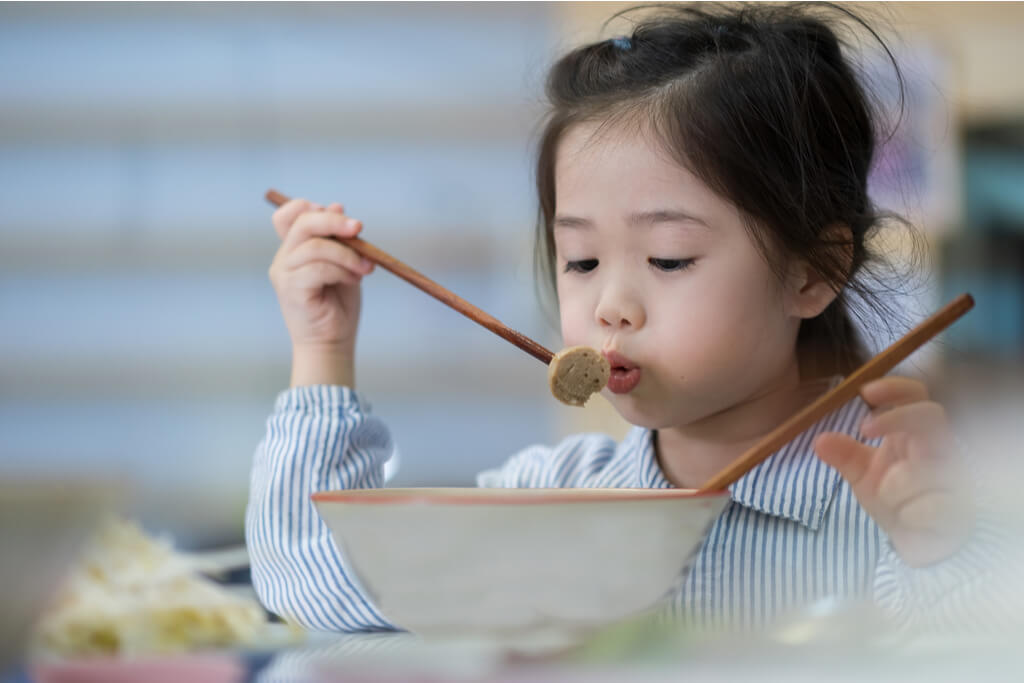 A little girl blows onto some food that she has stabbed a chopstick through over a bowl of the food.