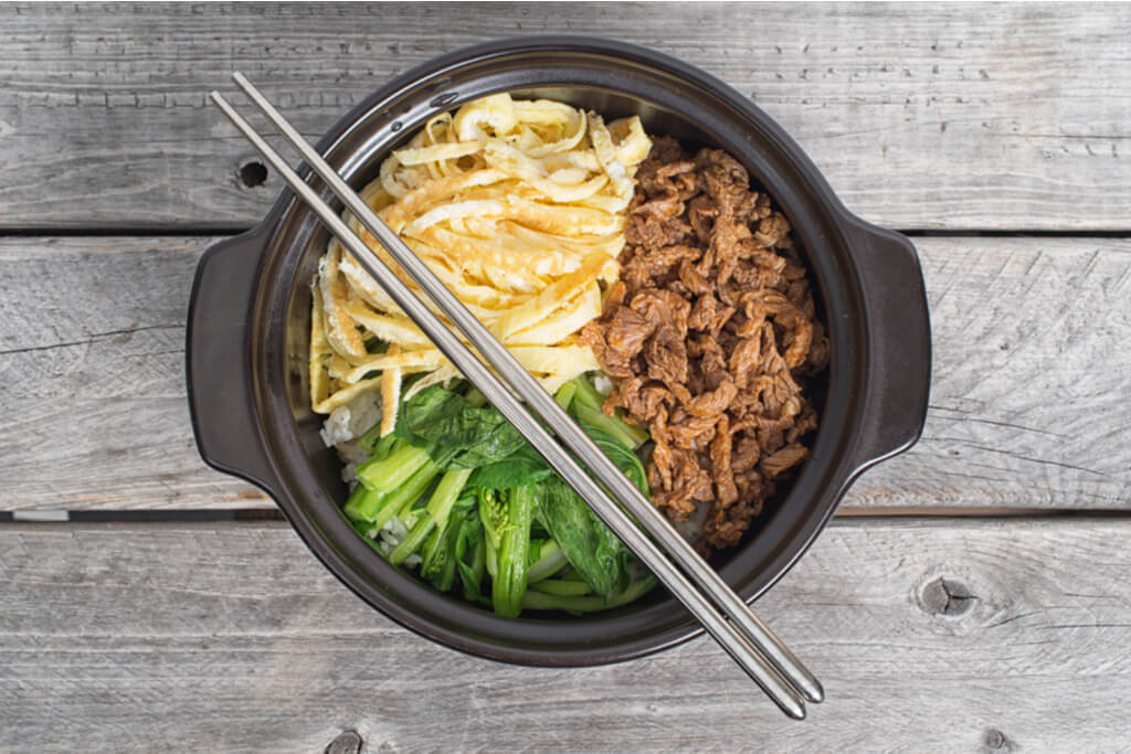 A bowl of Korean food with beef and vegetables with a pair of Korean metal chopsticks laid over it.