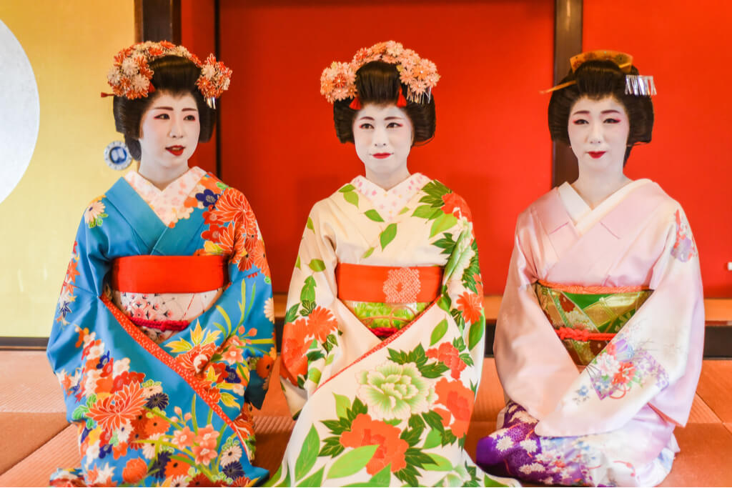 Three different maiko sit on the floor in front of a red door on tatami, with colorful kimonos.