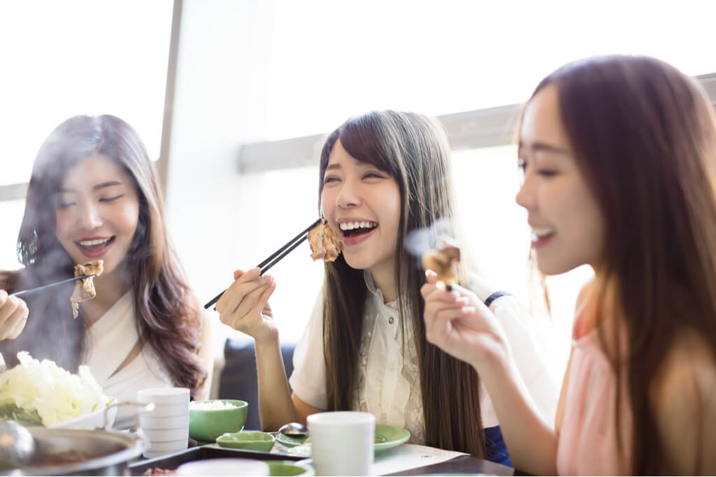Three women enjoy eating yakiniku at a restaurant while smiling and laughing.