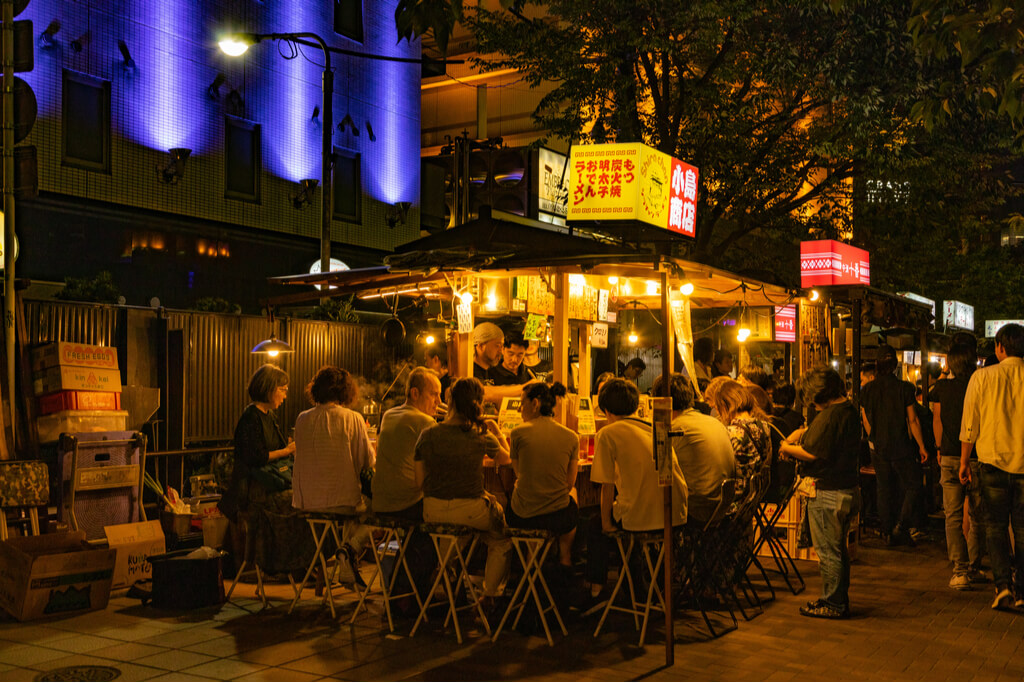 A food stand or yatai in Fukuoka serving Kyushu ramen to customers sitting around the stand on a busy street.