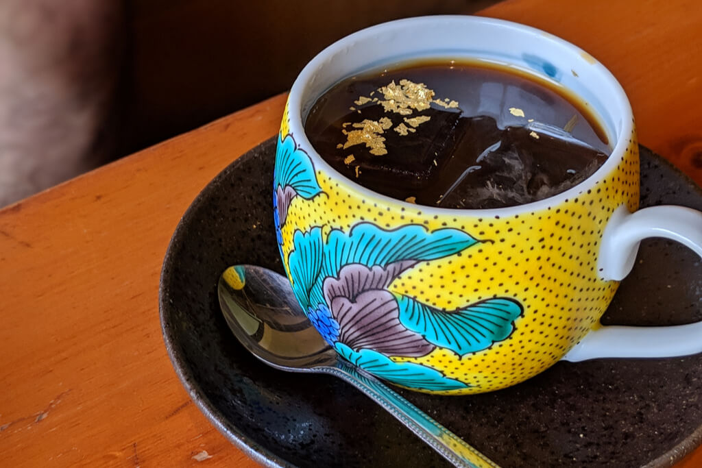 A colorful yellow, blue, green, and purple kutani cup filled with coffee with gold leaf sprinkles on a black plate on a wood table.