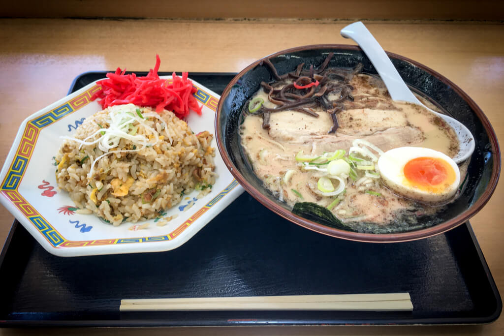 A bowl of Hakata style Kyushu Ramen with black pepper in the broth next to a plate of fried rice with red pickled ginger on a black tray on a counter