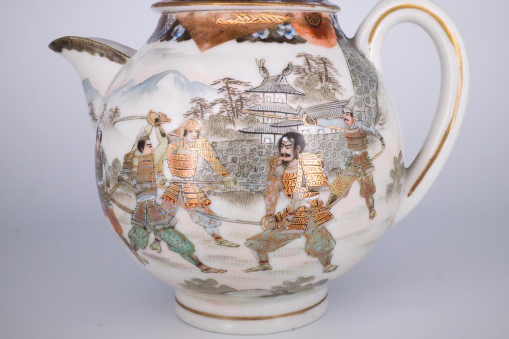 A kutani ware pot featuring a samurai battle scene utilizing gold leaf on a white background.