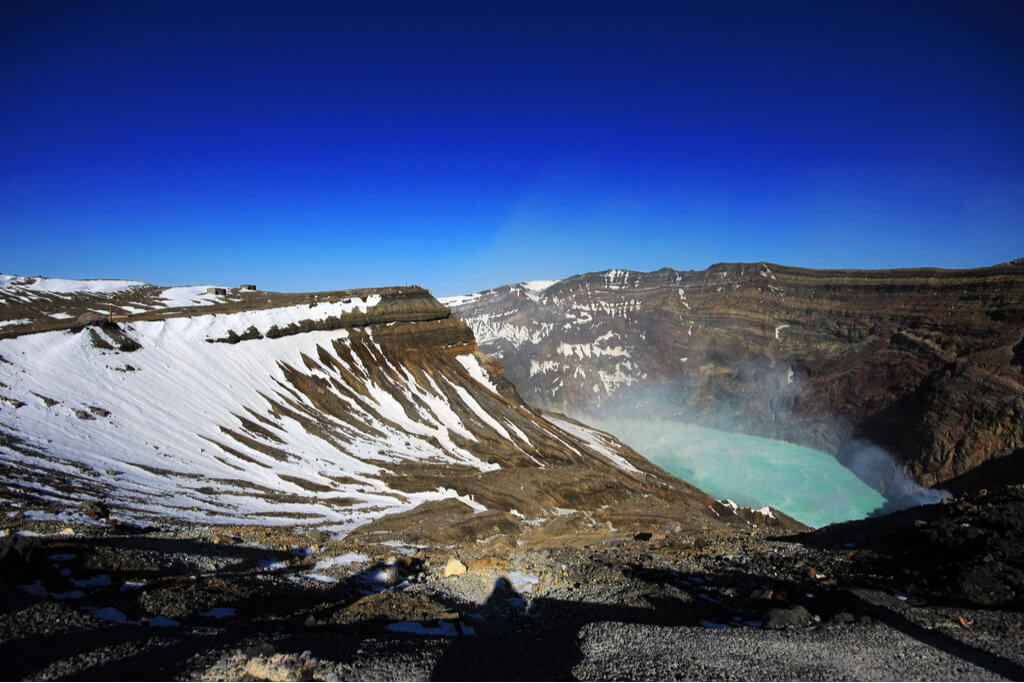 A picture of the top of the caldera of Mt. Aso with a pool of hot water steaming up and some snow around it