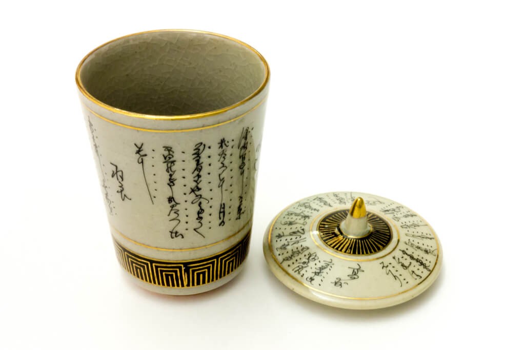 A beige kutani cup featuring traditional Japanese writing with black and gold accents on a white background