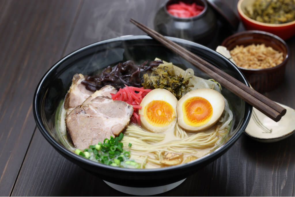 A bowl of Kyushu ramen with egg, pickled ginger, pork, and other toppings with extra toppings in the background.